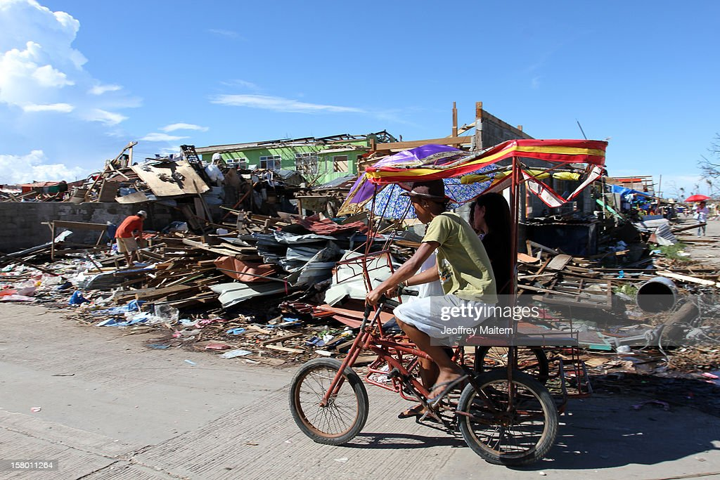 A man cycles past destroyed homes after Typhoon Bopha on December 8, 2012 the town of Cateel, Davao Oriental province, Philippines. More than 500 people have been killed and scores of others remain missing after Typhoon Bopha, the strongest storm to hit the Philippines this year, pounded the region. The United Nations Office for the Coordination of Humanitarian Affairs reported that about 5.3 million people are affected and 533 are missing. (Photo by Jeoffrey Maitem/Getty Images