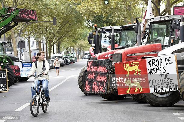 A man cycles past farmers' tractors parked on Place de la Nation in Paris during a national demonstration on September 3 to protest against the...