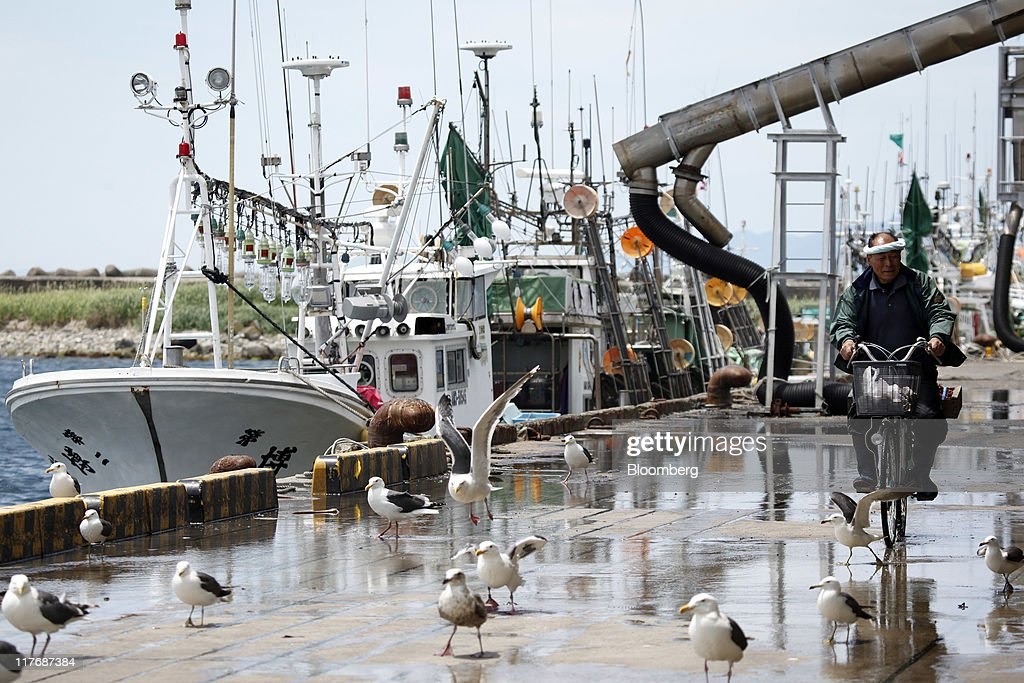 A man cycles past fishing boats moored at a fishing port in Oma Town, Aomori Prefecture, Japan, on Sunday, June 26, 2011. Over the 29 years since Electric Power Development Co.'s (J-Power) nuclear plant was proposed, Oma has received almost 11 billion yen in subsidies, said Kenichi Ito, a town planning official. In Oma and other Aomori towns, the grants helped offset declining revenues that threatened the survival of rural communities, officials said. Photographer: Kiyoshi Ota/Bloomberg via Getty Images