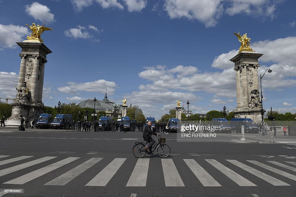A man cycles past French riot police during a demonstration against the government's planned labour law reforms on May 3, 2016, in Paris as French lawmakers begin to examine the contested labour reform bill at the Parliament. Unions fear it will erode the cherished rights of workers on full-time contracts, while student organisations -- who have been at the forefront of the protests -- believe it will fail to create 'real' jobs for young people.