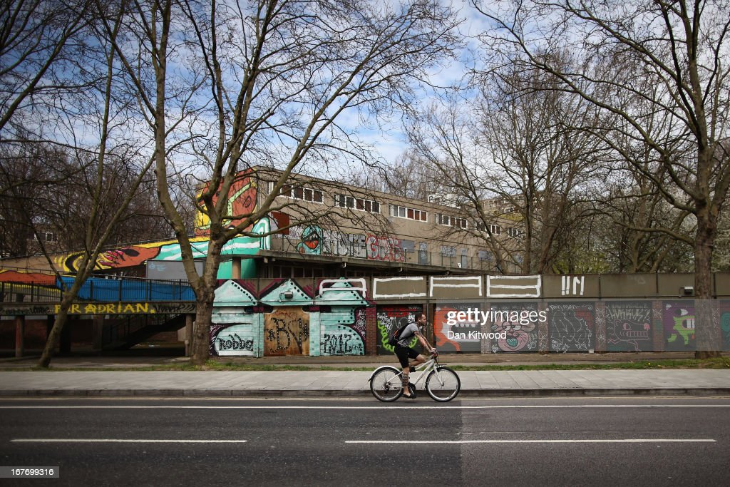 A man cycles past graffiti on the Heygate Estate in the Walworth area on April 24, 2013 in London, England. The Heygate estate in central London was built in 1974 as social housing and housed around 3000 people, but fell into a state of disrepair, gaining a reputation for crime and poverty. The estate is due to be demolished as part of the £1.5billion GBP 'Elephant & Castle regeneration scheme', and replaced with 2,500 'affordable' new homes. The area has become popular with street artists, storytellers, and guerilla gardeners and attracts an array of urban wildlife including bats, birds and mammals.