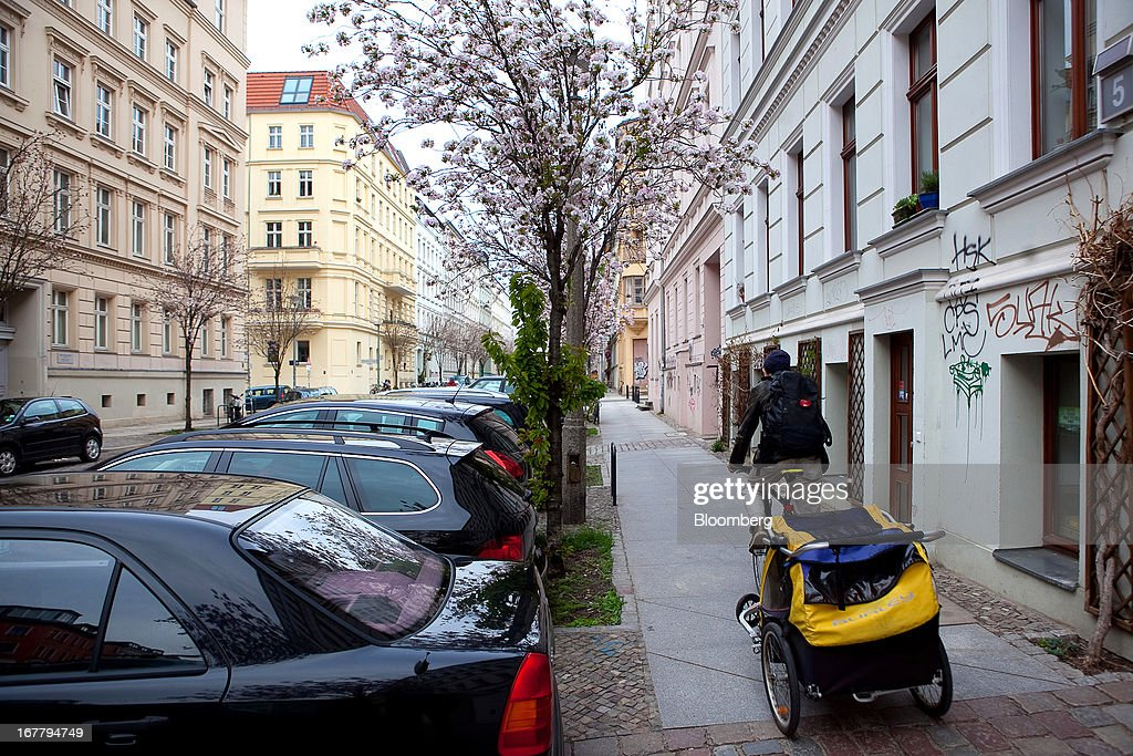 A man cycles past rows of residential housing located in the Mitte district of Berlin, Germany, on Monday, April 29, 2013. Rents and home prices in Germany's largest cities are rising at the fastest rate in twenty years, according to data compiled by Bulwien Gesa AG. Photographer: Krisztian Bocsi/Bloomberg via Getty Images