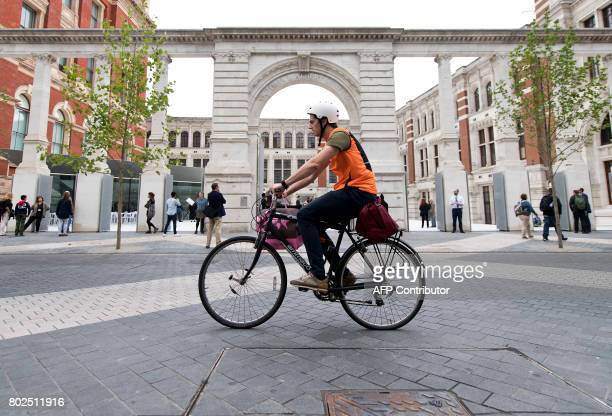A man cycles past the entrance to the Sackler Courtyard a new addition to the Victoria and Albert museum as it is unveiled to the public in London on...