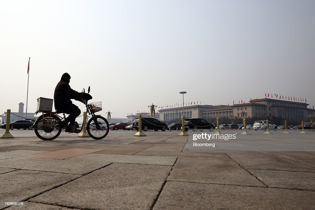 A man cycles past the Great Hall of the People in Beijing, China, on Thursday, March 14, 2013. Xi Jinping was named China's president by the national legislature, replacing Hu Jintao in the country's most rapid formal transfer of power in more than a generation. Photographer: Tomohiro Ohsumi/Bloomberg via Getty Images