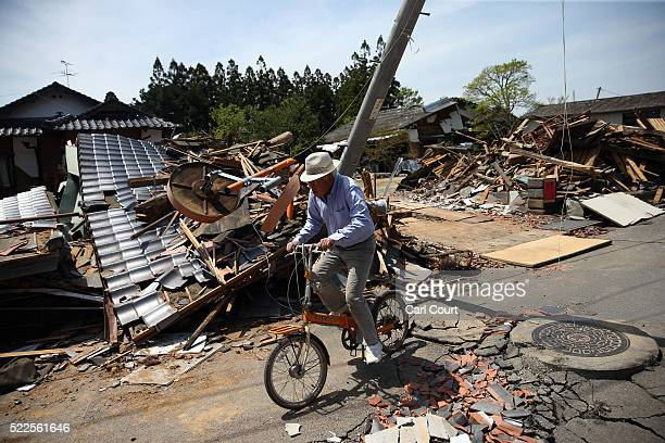A man cycles past the rubble of a collapsed house following an earthquake on April 20 2016 in Mashiki near Kumamoto Japan As of April 20 48 people...
