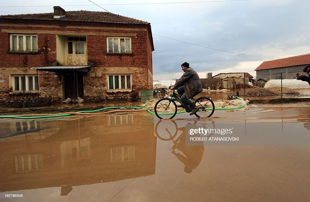A man cycles through a flooded alley in the village of Murtino, in the southeastern tip of the Republic of Macedonia on February 27, 2013. The torrential rains which in the last three days poured down on the fertile Strumica Valley inundated fields and villages, destroying or damaging crops and households. Tens of people in the region are now sheltered, as their homes were gravely damaged.