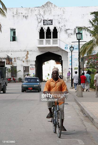 A man cycles through Stone Town on November 8 2011 in Zanzibar Tanzania Prince Charles Prince of Wales and Camilla Duchess of Cornwall are on a four...