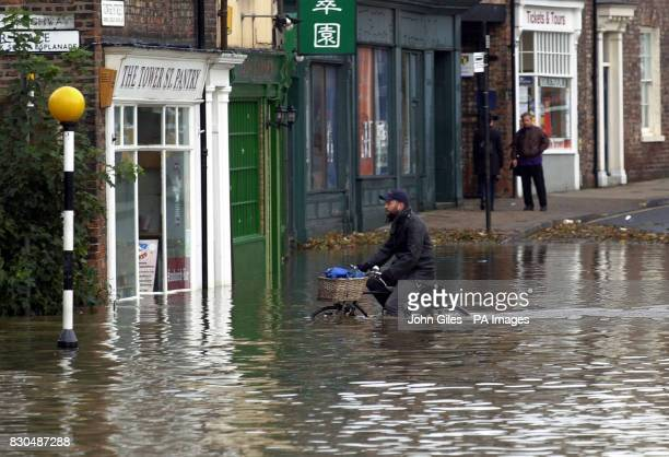 A man cycles through the floodwaters in York where more than 150 businesses have been disrupted and 100 people evacuated as the city was hit by its...