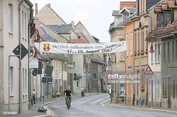 A man cycles through the Friedrichstrasse road in Muegeln eastern Germany 20 August 2007 where a banner still promotes the town's festival German...