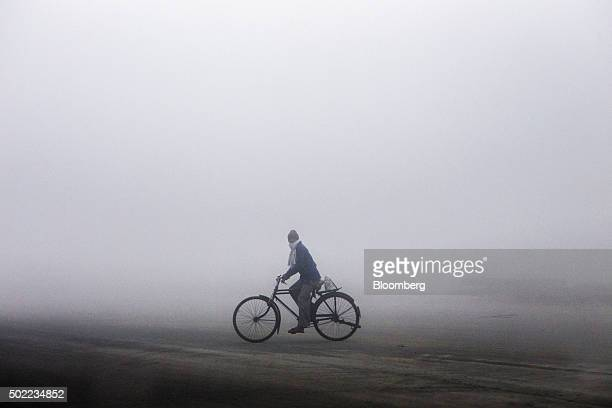 A man cycles through the smog on National Highway 1 in Karnal Haryana India on Tuesday Dec 8 2015 Air pollution claims an estimated 650000 lives...