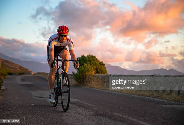 Man cycling at sunset, Corsica, France