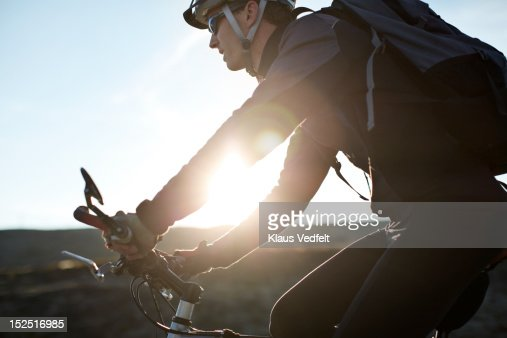 Man cycling in the sunset, cropped tight : Stock Photo