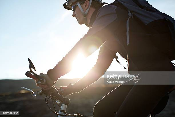 Man cycling in the sunset, cropped tight