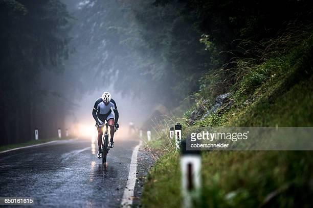 Man cycling on a wet road in rain, Salzburg, Austria