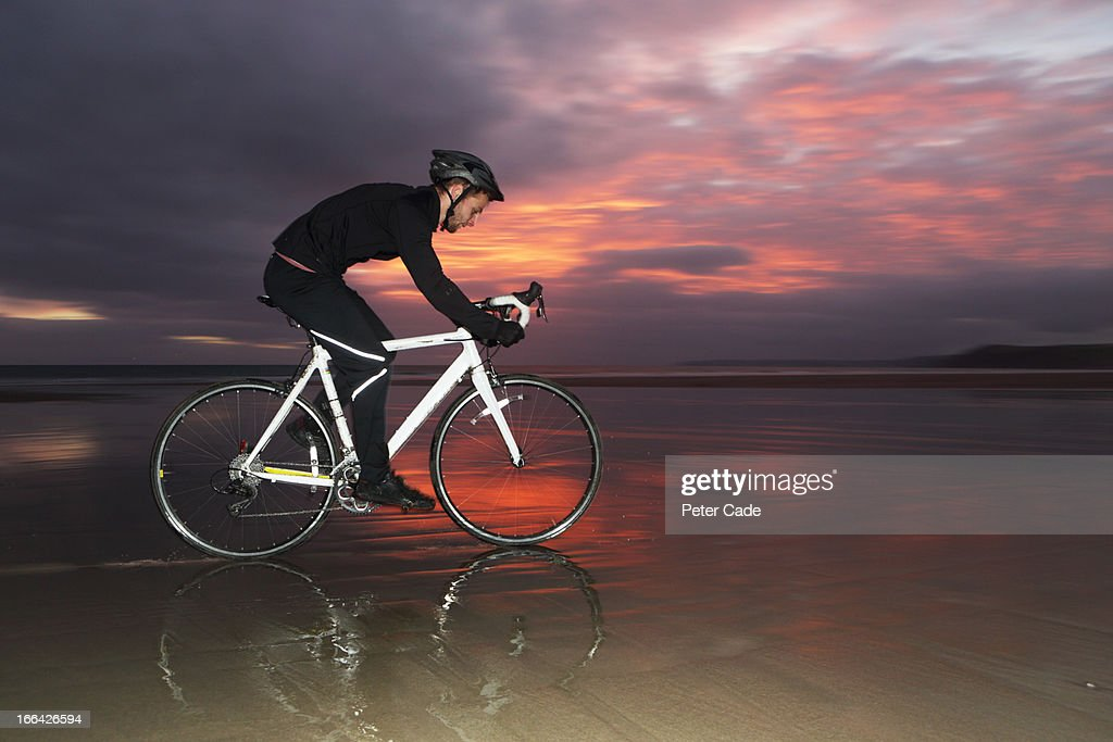 Man cycling on beach at sunset : Stock Photo