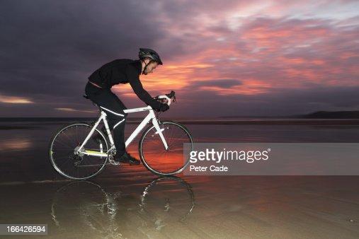 Man cycling on beach at sunset : Stockfoto