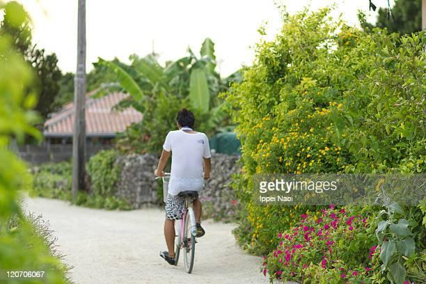 Man cycling, Taketomi Island, Okinawa, Japan