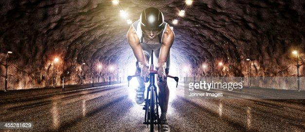 Man cycling through tunnel