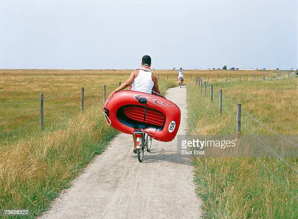 A man cykling carrying a rubber dinghy.