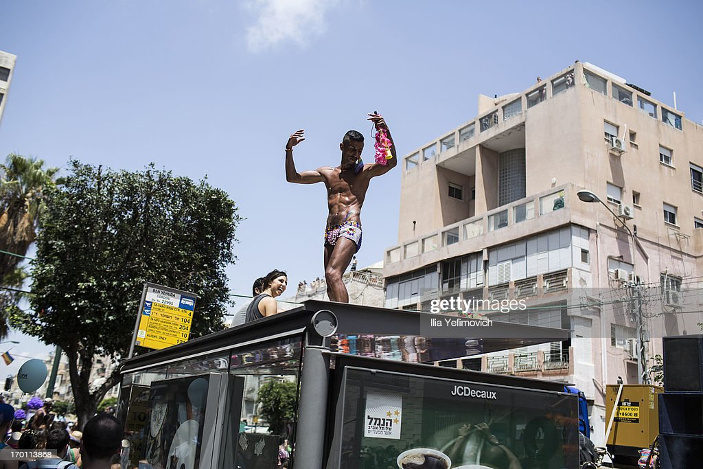 A man dances on a bus stop during the annual Tel Aviv Gay Pride parade on June 7, 2013 in Tel Aviv, Israel. Thousands of people gathered in Tel Aviv for the parade, which attracts visitors from all over the world.