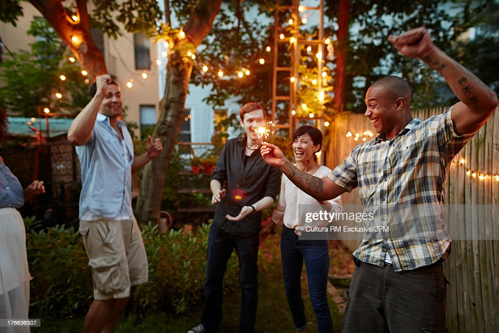 Man dancing and holding sparklers at garden party
