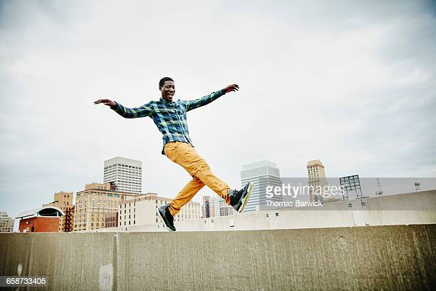 Man dancing on top of wall on rooftop