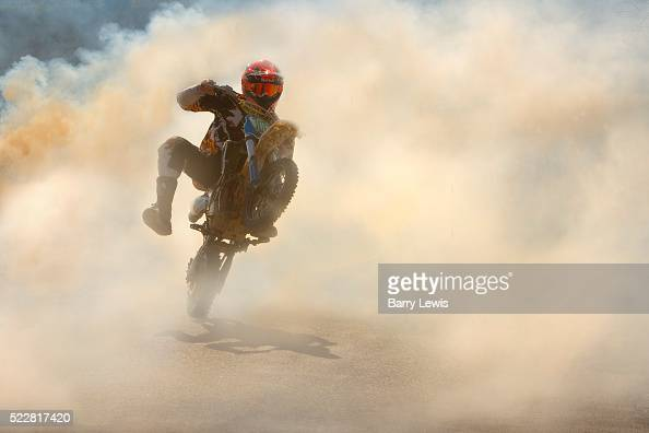 Man dangerously doing a wheelie on his motorbike through the smoke created from the springtime burning of the grass verges on the roadside in...