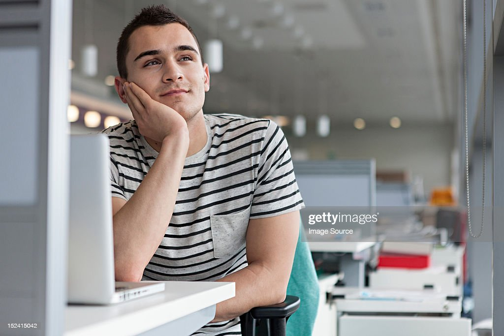 Man daydreaming at desk : Stock Photo
