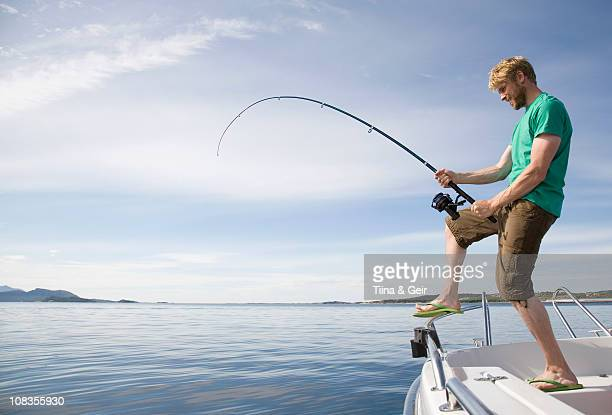 Man deep-sea fishing from boat