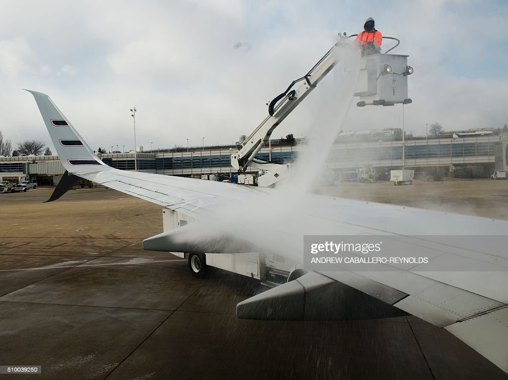 A man de-ices a planes wing after a snow storm at Ronald Regan National Airport in Washington, DC, on February 13, 2016. / AFP / ANDREW CABALLERO-REYNOLDS