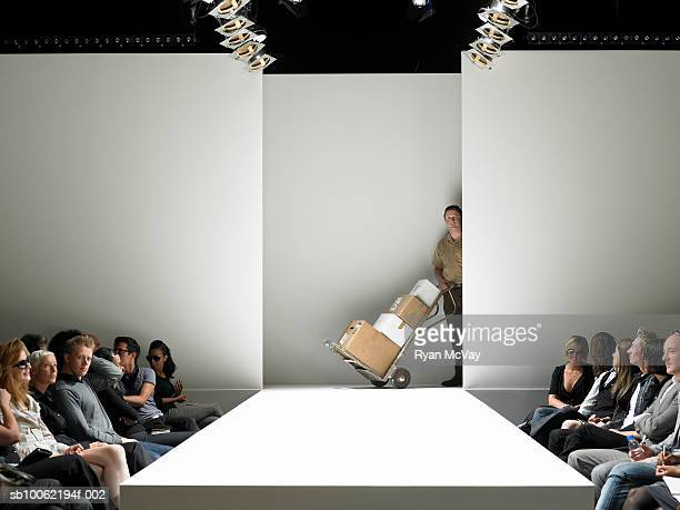 Man delivering boxes on catwalk