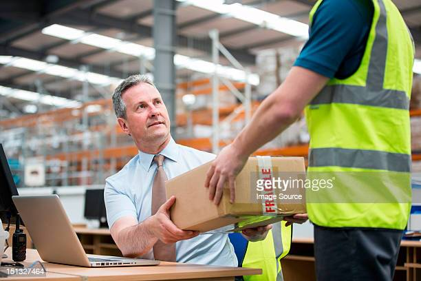 Man delivering cardboard box to another man