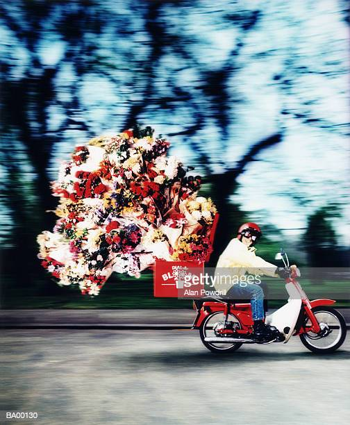 Man delivering floral bouquets on scooter, blurred motion