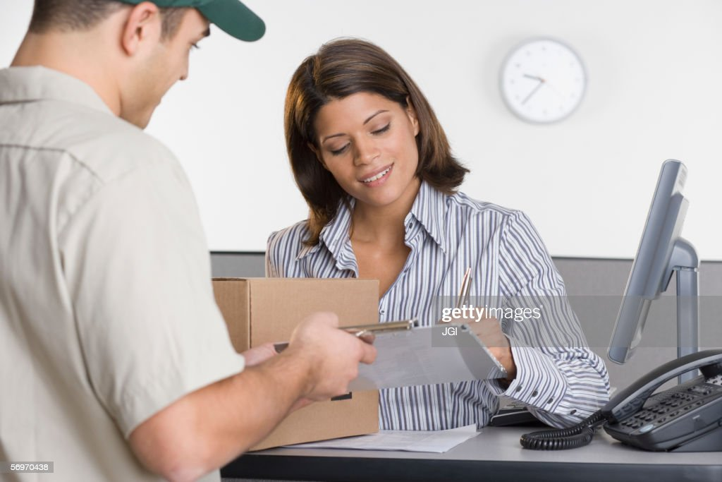 Man delivering package for woman to sign for : Stock Photo