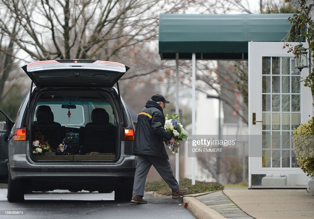 A man delivers flowers at Abraham L. Green and Son Funeral Home in in Fairfield, Connecticut, December 17, 2012 for Noah Pozner,6 one of the victims of the elementary school shooting in Newtown, Connecticut. Funerals began Monday after the school massacre that took the lives of 20 small children and six staff, triggering new momentum for a change to America's gun culture. The first burials, held under raw, wet skies, were for two six-year-old boys who were among those shot in Sandy Hook Elementary School. On Tuesday, the first of the girls, also aged six, was due to be laid to rest. There were no Monday classes at all across Newtown, and the blood-soaked elementary school was to remain a closed crime scene indefinitely, authorities said. AFP PHOTO/Don Emmert