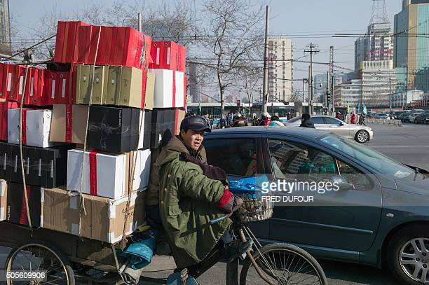 TOPSHOT A man delivers goods in the street of Beijing on January 19 2016 China's economy grew at its slowest pace in a quarter of a century last year...