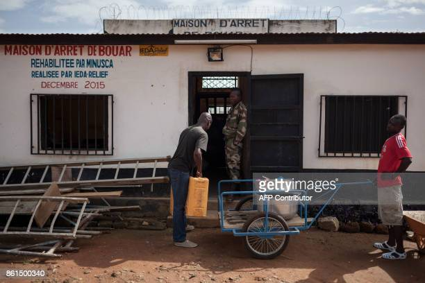 A man delivers porridge for breakfast for the detainees at the Bouar detention centre in Bouar western Central African Republic on October 13 2017 In...