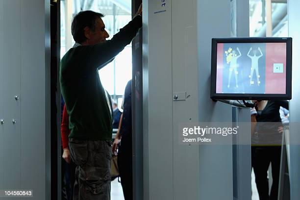 A man demonstrates a check by a full body scanner at Hamburg Airport on September 30 2010 in Hamburg Germany Two scanners are being tested at...