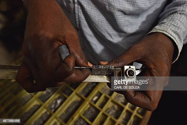 A man demonstrates how to load individual letters onto an old original Heidelberg printing press at the Daha printing press in Mogadishu on March 26...
