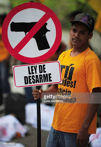 A man demonstrates in favour of a civilian disarmament law during a protest against insecurity and violence in the Venezuelan capital in Caracas on...