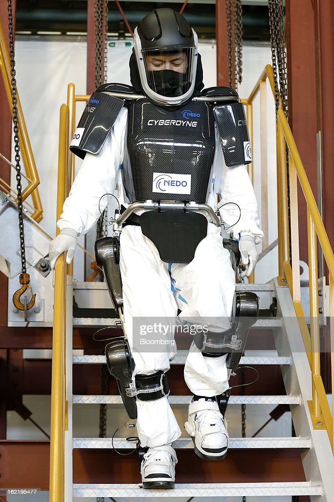 A man demonstrates the Hybrid Assistive Limb (HAL) work-assist robot suit, developed by Cyberdyne Inc. in the New Energy and Industrial Technology Development Organization's (NEDO) unmanned anti-disaster system research and development project, during a media review at Chiba Institute of Technology's (CIT) Shibazono campus in Narashino City, Chiba Prefecture, Japan, on Wednesday, Feb. 20, 2013. NEDO, Japan's largest public R&D management organization, introduced its latest disaster response robot technologies today. Photographer: Kiyoshi Ota/Bloomberg via Getty Images
