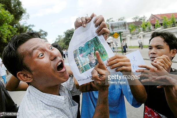 A man demonstrating against the Burmese military junta shows the finger in front of a picture of a Burmese officer