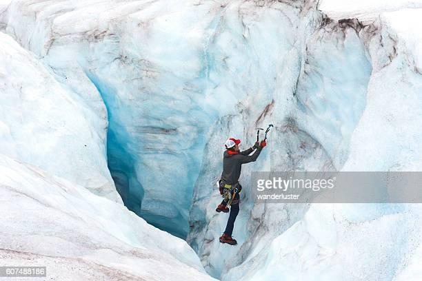 Man descends a giant moulin on a glacier