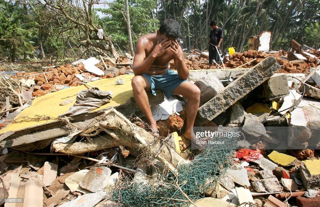 A man despairs as he searches amongst the remains of his house after a massive tsunami wave swept across coastal Sri Lanka on December 30 2004 in...
