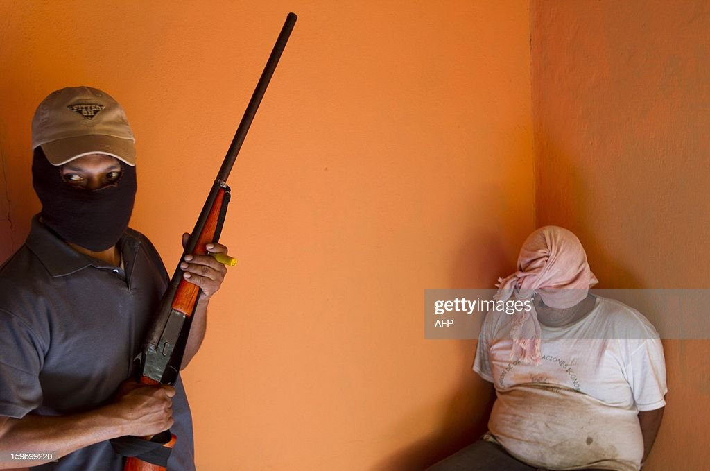 A man detained by residents of Ayutla de los Libres forming their own vigilante police forces, is watched at a house in this town in the Mexican southern state of Guerrero, on January 18, 2013. Hundreds of civilians armed with rifles, pistols and machetes decided to provide security for the communities of Tecoanapa and Ayutla de los Libre in the state of Guerrero, saying gangs were committing robberies, kidnappings and murder. The vigilante force has put up checkpoints on roads and conducts night watches in the towns. Guerrero, home to the Pacific resort town of Acapulco, has been one of the states hardest hit by Mexico's drug violence, which has left more than 70,000 people killed across the country since 2006. AFP PHOTO/Pedro Pardo