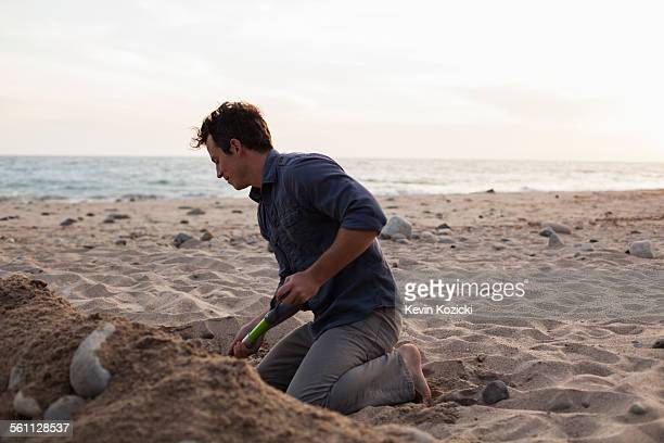 Man digging into sand on beach