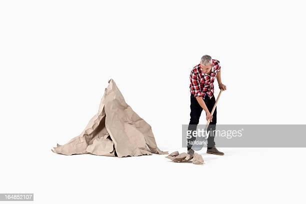 A man digging up construction paper rock, next to an artificial paper boulder