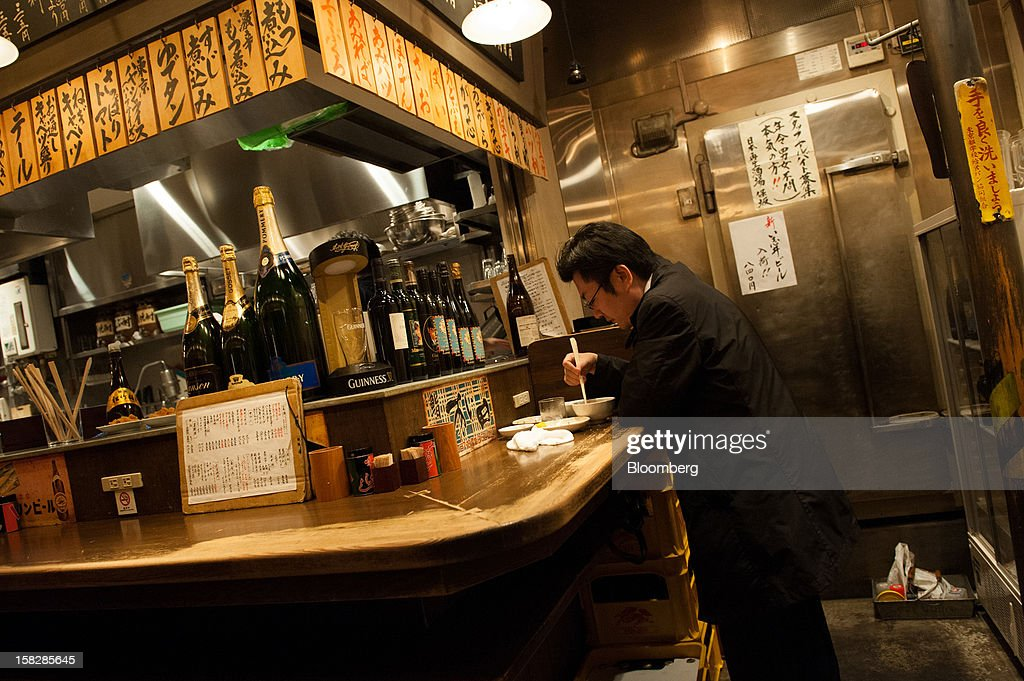 A man dines at a pub in Tokyo, Japan, on Monday, Dec. 10, 2012. Japan's economy shrank in the last two quarters, meeting the textbook definition of a recession, as the dispute with China, the country's biggest export market, caused consumers there to shun Japanese products and contributed to Japan's worst year for exports since the global recession in 2009. Photographer: Noriko Hayashi/Bloomberg via Getty Images