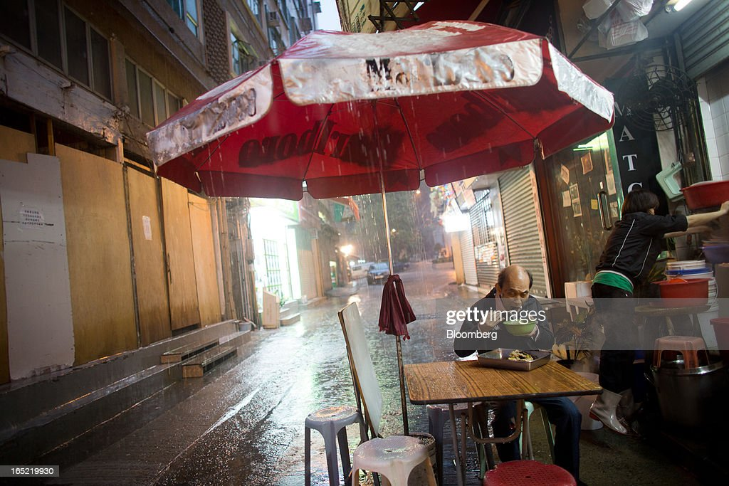 A man dines under an umbrella at an eatery in the Tai Hang area of Hong Kong, China, on Saturday, March 30, 2013. Rents are climbing in neighborhoods near Causeway Bay and Hong Kong's other prime shopping districts, known for luxury stores that attract free-spending tourists from mainland China. That's squeezing out mom-and-pop shops, congee and noodle vendors as developers and landlords seek to profit from the trend. Photographer: Lam Yik Fei/Bloomberg via Getty Images