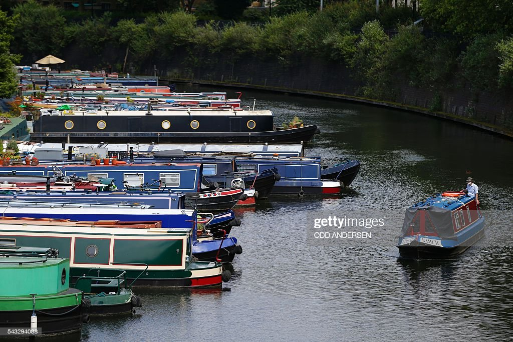 A man directs his houseboat past other moored boats on Regent's Canal in London on June 27, 2016. / AFP / Odd ANDERSEN